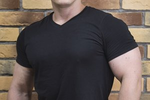 Attractive and muscular athlete - portrait of young handsome sportsman near brick wall