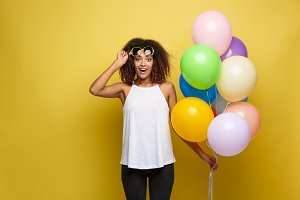 Celebration Concept - Close up Portrait happy young beautiful african woman with white t-shirt surprising expression with colorful party balloon. Yellow Pastel studio Background.
