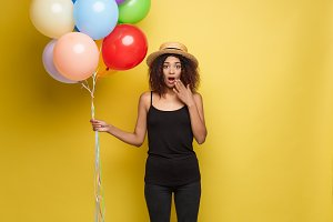 Celebration Concept - Close up Portrait happy young beautiful african woman in black t-shirt surprising with colorful party balloon. Yellow Pastel studio Background.