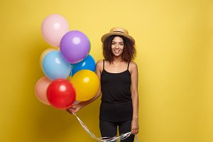 Celebration Concept - Close up Portrait happy young beautiful african woman in black t-shirt smiling with colorful party balloon. Yellow Pastel studio Background.