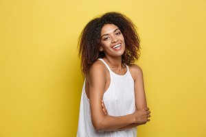 Headshot portrait of beautiful attractive African American woman posting crossed arms with happy smiling. Yellow studio background. Copy Space.