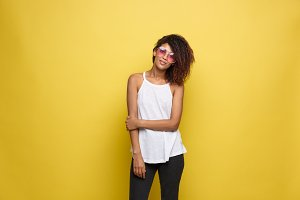 Beautiful attractive African American woman with trendy glasses posting over yellow studio background. Copy Space.