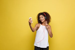 Lifestyle Concept - Portrait of beautiful African American woman joyful listening to music and take a photo on mobile phone. Yellow pastel studio background. Copy Space.