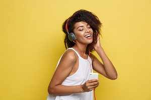 Lifestyle Concept - Portrait of beautiful African American woman joyful listening to music on mobile phone. Yellow pastel studio background. Copy Space.