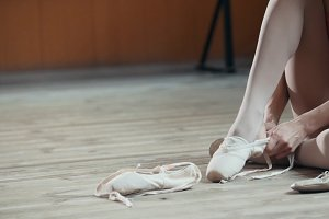 Girl balerina dancer putting on her ballet shoes