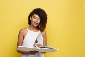 Education Concept - Portrait of African American woman reading a book. Yellow studio background. Copy Space.