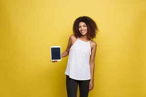 Lifestyle Concept - Portrait of beautiful African American woman joyful presenting something on electronic tablet. Yellow pastel studio background. Copy Space.