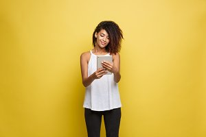 Lifestyle Concept - Portrait of beautiful African American woman joyful reading something on electronic tablet. Yellow pastel studio background. Copy Space.