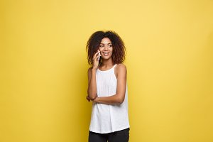 Lifestyle Concept - Portrait of beautiful African American woman joyful talking on mobile phone with friend. Yellow pastel studio background. Copy Space.