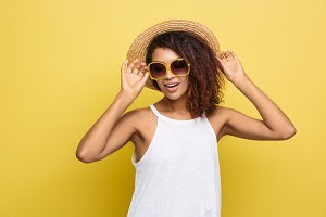 Travel concept - Close up Portrait young beautiful attractive African American woman with trendy hat and sunglass smiling. Yellow Pastel studio Background. Copy space.