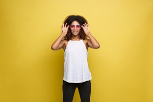 Travel concept - Close up Portrait young beautiful attractive African American woman with trendy sunglass smiling. Yellow Pastel studio Background. Copy space.