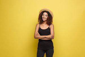 Travel concept - Close up Portrait young beautiful attractive African American woman with trendy hat smiling and joyful expression. Yellow Pastel studio Background. Copy space.