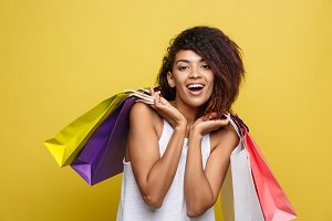 Shopping Concept - Headshot of Portrait young beautiful attractive African woman smiling and joyful with colorful shopping bag. Yellow Pastel wall Background. Copy Space.