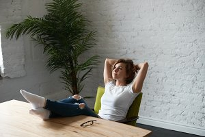Relax time at work. When you did all deal and ready for a holiday. Dreaming concept at lunch time on the job. Woman legs on the desk. Stylish girl in white t-shirt and blue jeans.