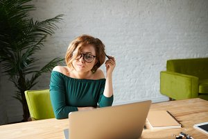 Pretty woman in green dress working at laptop and dream how to spend weekend with boyfriend. Attractive female manager sitting at desk after hard working day. European businesswoman read social news.