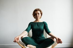 Time for relax in yoga chair after hard working week. Feeling calm. Girl in lotus pose with close eyes. Keep positive energy from space. woman meditating indoor before sunrise.