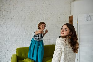Two young female friends having fun indoors: pretty girl with curly hair turning face and looking at camera while her best friend standing on sofa in background and pointing her index finger at viewer