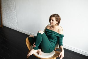 People and lifestyle. Indoor shot of beautiful gorgeous young female with charming cute smile relaxing in her room, sitting on designer's chair, dressed in dark-green off-the-shoulder jumpsuit