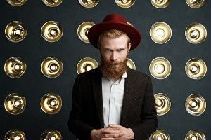 Portrait of mysterious young redhead man with fuzzy beard wearing red hat and elegant suit standing at studio wall decorated with lamps, clasping hands in front of his stomach and looking at camera