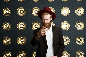 Handsome young redhaired bearded European musician in stylish headwear and dark jacket posing against background of lamps decoration and pointing finger at camera, having serious face expression
