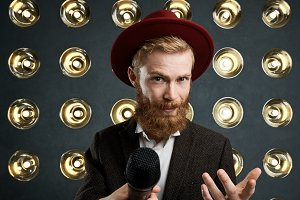 Horizontal shot of handsome bearded performer or showman wearing stylish red hat and suit performing in front of audience, singing or speaking into microphone, standing over wall with round lamps