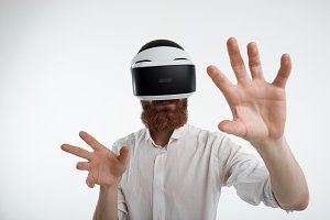 Bearded Caucasian businessman in white shirt using oculus headset, experiencing virtual reality in office, gesturing as if touching something. 3d technology, cyberspace and entertainment concept