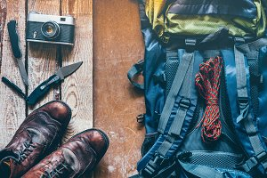 Hiking accessories on old wooden background: old hiking leather boots, backpack, vintage film camera, knifes. Lifestyle concept adventure vacations outdoor. Flat lay style