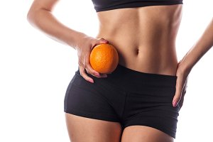 Slim woman holds an orange.
