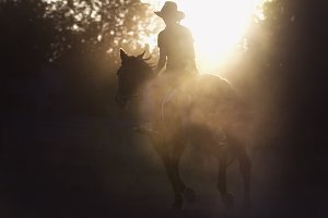 Silhouette of a woman riding a horse - sunset or sunrise, horizontal