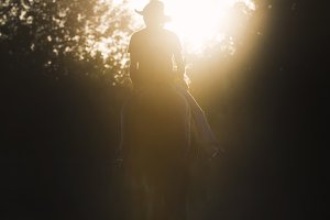 Jockey - silhouette of a woman riding a horse - sunset or sunrise - vertical