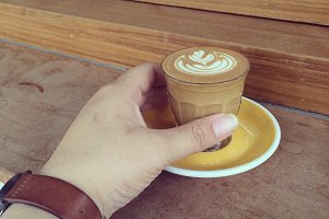 hand grabs cappuccino or latte