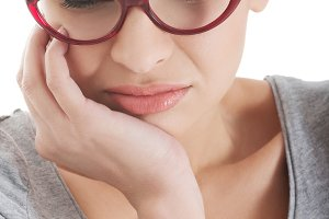Young beautiful woman in eyeglasses with toothache.