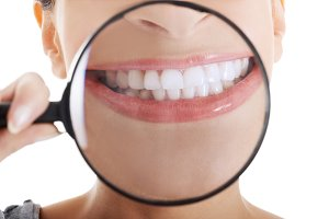 Beautiful woman with magnifying glass showing her perfect white teeth.