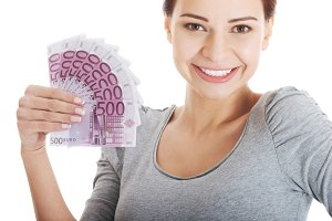 Beautiful young woman holding large sum of money.