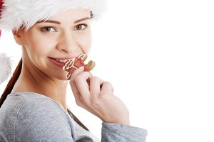 Young beautiful woman in santa hat eating gingerbread cookie.
