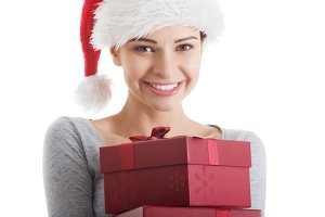 Young beautiful woman in santa hat holding presents.