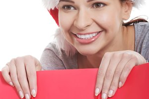 Young beautiful woman in santa hat in red shopping bag.