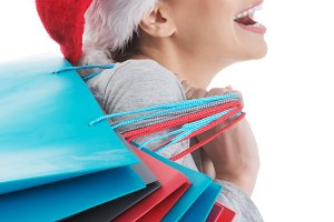 Beautiful woman in santa hat with shopping bags.