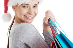 Young beautiful woman in santa hat with shopping bags.