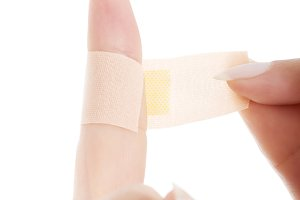 Woman's finger with adhesive tape.