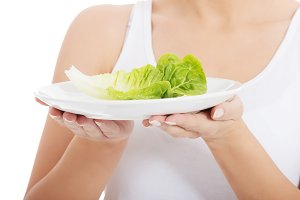 Young slim woman with lettuce on a plate.