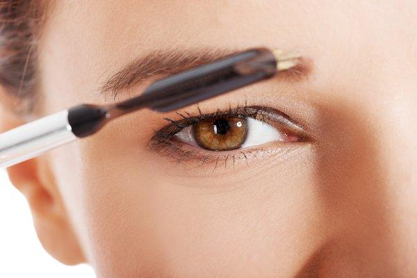 Beautiful woman brushing her eyebro…