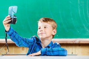Schoolboy make selfie at blackboard in school