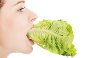 Young beautiful slim woman eating lettuce.
