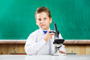 Smart stylish schoolboy used microscope on lesson