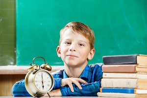 Small boy sitting with alarm clock near blackboard