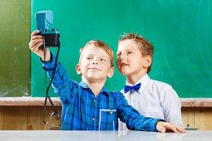 Two schoolboys make selfie at blackboard in school