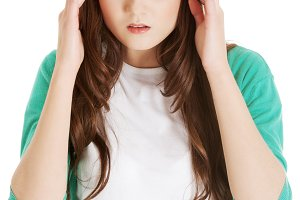 Young casual woman is having headache.