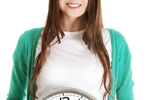 Young casual woman holding clock.