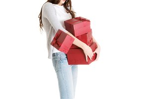 Young casual woman holding stock of presents.
